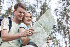 Happy young backpackers reading map in forest Stock Photography