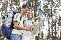 Happy young backpackers reading map in woods Stock Image
