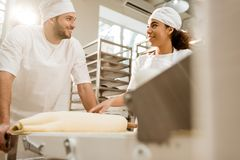 Happy young bakers working with industrial dough roller. At baking manufacture royalty free stock images