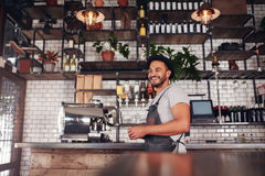 Happy young bar owner standing at the counter Stock Image