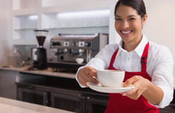 Happy young barista offering cup of coffee smiling at camera Stock Photos