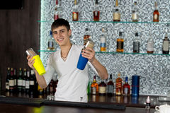 Happy young barman mixing cocktails royalty free stock photos