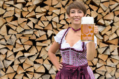 Happy young Bavarian woman toasting with a beer. Happy young Bavarian woman in a traditional dirndl dress standing in front of stacked woodpile toasting with a Royalty Free Stock Photography