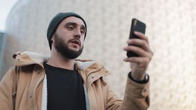 Happy young beard man having video chat holding smartphone webcam chatting with friends. Outside