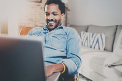 Happy young bearded African man spending rest time at home and using laptop.Concept of people enjoying mobile devices stock image