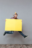 Happy young bearded birthday man holding copyspace board jumping Royalty Free Stock Images