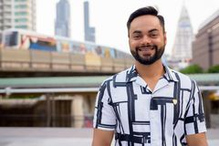 Free Happy Young Bearded Indian Man Smiling Against View Of Train At Sky Train Station Stock Image - 143054101