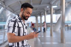 Happy young bearded Indian man using phone on the footbridge outdoors. Portrait of young bearded Indian man exploring in the city outdoors stock photography