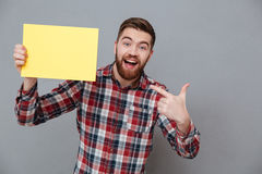 Happy young bearded man holding copyspace blank. Picture of happy young bearded man holding copyspace blank and pointing standing over grey background Stock Image