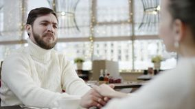 Happy young man talks to his girlfriend holding her hand by restaurant table. Happy young bearded man talks to his girlfriend holding her hand by restaurant stock footage