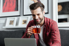 Happy young bearded man using laptop computer drinking tea Stock Photos