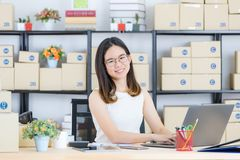 Asian business lady at office. Happy, young, beautiful, Asian business lady, long black hair, wearing eyeglasses, in casual fashion, typing on notebook, sending stock photo