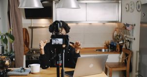 Happy young beautiful black lifestyle blogger woman making new entertainment video with camera at home slow motion. Edutainment and vlogging as a modern stock footage
