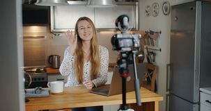 Happy young beautiful blonde female fashion blogger filming new vlog video for social media at home slow motion. Professional vlogger woman making a new blog stock video footage