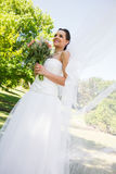 Happy young beautiful bride with bouquet in park Stock Photography