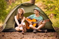Happy young beautiful couple sitting with guitar in forest at tent. happy man confesses love stock images