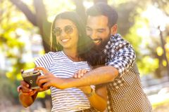 Happy young beautiful couple taking photos royalty free stock photography