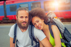 Happy young and beautiful couple of tourists sitting at the rail. Happy young and beautiful couple of tourists with backpacks sitting at the railway station near Stock Photography