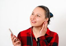 Happy young beautiful girl in red plaid shirt listening to music in headphones and smiling. On white background stock photography