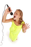 Happy young beautiful girl singing with microphone Stock Photo