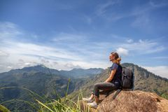 Happy young beautiful girl tourist with a backpack. Sit in the mountains and enjoy the view and nature royalty free stock image