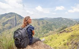 Happy young beautiful girl tourist with a backpack. Sit in the mountains and enjoy the view and nature stock images