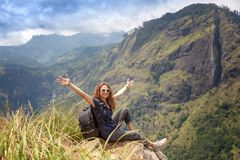 Happy young beautiful girl tourist with a backpack. Sit in the mountains and enjoy the view and nature royalty free stock photo