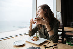 Happy young beautiful lady sitting in cafe drinking coffee. Royalty Free Stock Photography