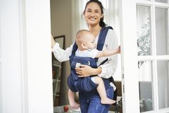Cheerful mother opening front door royalty free stock image