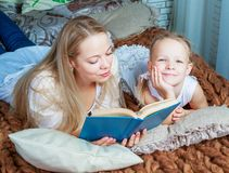 Mother and daughter reading. Happy young beautiful mother and daughter reading a book at home Stock Image