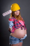 Happy young beautiful pregnant woman in builder's helmet with  p Stock Photo