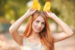 Happy young, beautiful red-haired girl in autumn park. Royalty Free Stock Photo