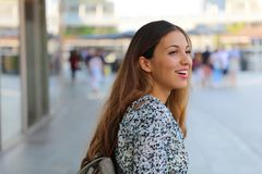 Happy young beautiful urban woman looking to the side with blurred city background royalty free stock image