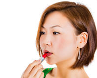Happy young beautiful woman applying lipstick at home Stock Photo