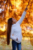 Happy young beautiful woman in autumn park on sunny day, pointing finger on the tree, Young woman in white coat during sunset in t Royalty Free Stock Image