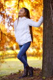 Happy young beautiful woman in autumn park on sunny day, Young woman in white coat during sunset in the park Royalty Free Stock Photo