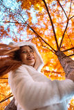 Happy young beautiful woman in autumn park on sunny day, Young woman in white coat during sunset in the park Royalty Free Stock Photography
