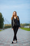 Happy young beautiful woman in black leather jacket black jeans slip-on posing for model tests in the summer park Royalty Free Stock Photography