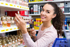 Happy young beautiful woman choosing fragrance. On display and smiling Royalty Free Stock Photo