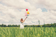 Happy young beautiful woman holding balloons in the grass field. Beautiful woman holding balloons in the grass field enjoy with fresh air Royalty Free Stock Photography