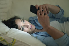 Happy young beautiful woman on home couch using mobile phone texting or enjoying app Royalty Free Stock Photography