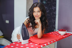Happy young beautiful woman ironing clothes. Royalty Free Stock Photo