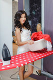 Happy young beautiful woman ironing clothes. Stock Images