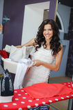 Happy young beautiful woman ironing clothes. Royalty Free Stock Photos