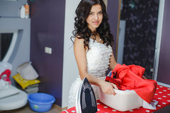 Happy young beautiful woman ironing clothes. Stock Image