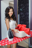 Happy young beautiful woman ironing clothes. Royalty Free Stock Photography