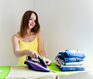 Happy young beautiful woman ironing clothes. Royalty Free Stock Images