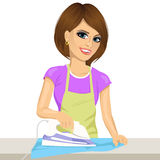 Happy young beautiful woman ironing clothes. Housework Royalty Free Stock Photo