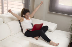 Happy Young beautiful woman with laptop on sofa arms up Stock Photography