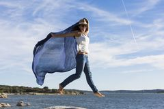 Free Happy Young Beautiful Woman Playing With A Blue Shawl At The Beach. Fun, Wind And Lifestyle Stock Photo - 155725110